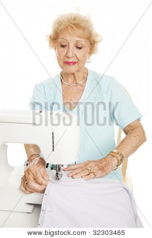 Elderly woman sews with her sewing machine.  Isolated on white.