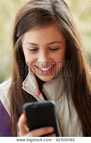 Teenage Girl Texting On Smartphone Wearing Winter Clothes