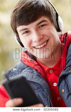 Teenage Boy Wearing Headphones And Listening To Music Wearing Winter Clothes