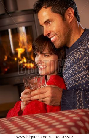 Middle Aged Couple Sitting On Sofa Watching TV By Cosy Log Fire