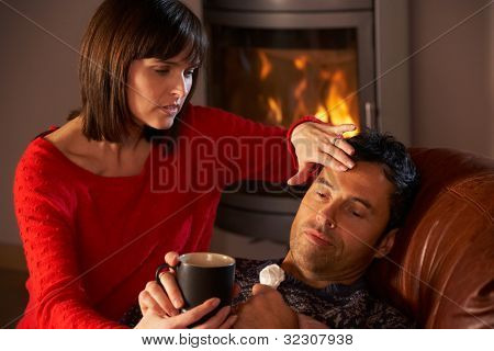 Wife Nursing Sick Husband With Cold Resting On Sofa By Cosy Log Fire