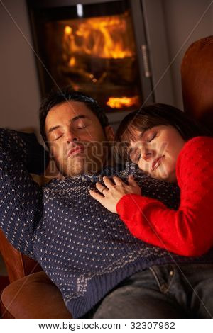 Middle Aged Couple Cuddling On Sofa By Cosy Log Fire