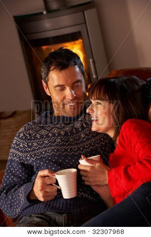 Middle Aged Couple Sitting On Sofa By Cosy Log Fire With Hot Drink
