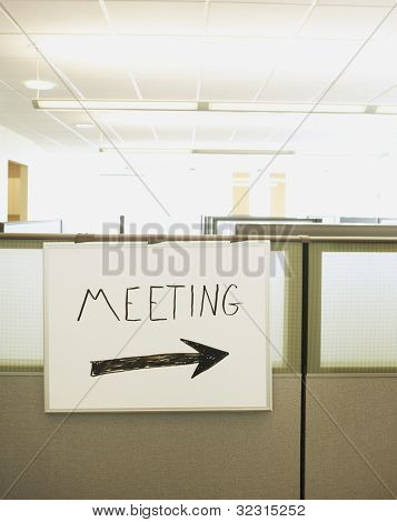 Dry erase board with Meeting written on it and an arrow