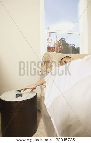 Man turning off a travel alarm clock from bed