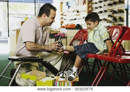 Young Hispanic boy trying shoes at shoe store