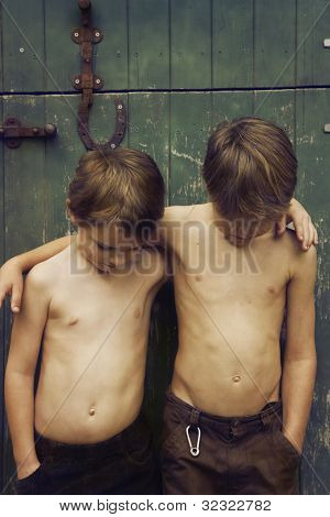 Two young brothers with arms around each other next to barn