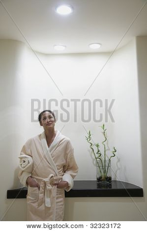 Woman in bathrobe standing in spa alcove