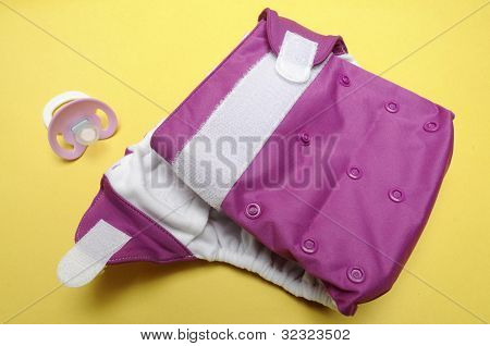 Open Eco Friendly Cloth Diaper With Dummy On Yellow Background