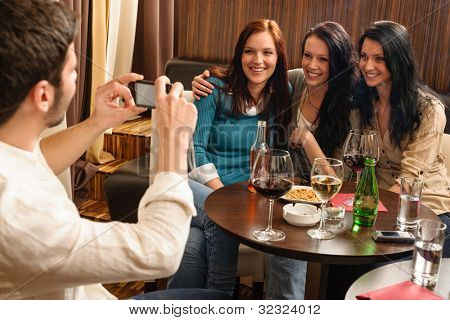 Young friends at the bar man take picture of three women