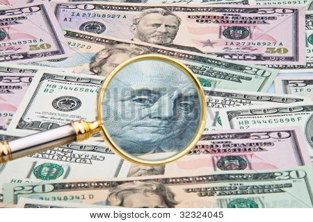 many dollar bills photographed with a magnifying glass. close up