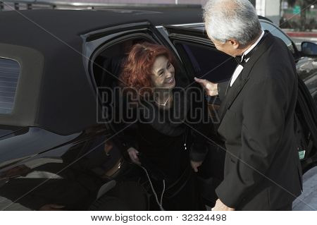 Senior Asian couple getting out of limousine
