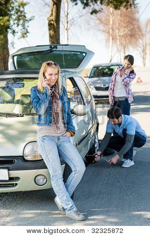 Homem de roda quebrada mudar pneu ajuda de dois amigos feminino