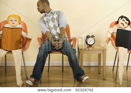 African man sitting in waiting area next to blowup dolls