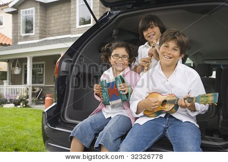 Siblings sitting on tailgate of car playing toy instruments