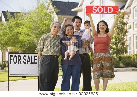 Multi-generational Asian family holding up Sold sign in front of house