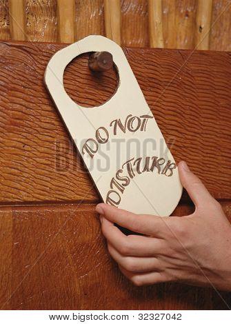 Hand putting Do Not Disturb sign on doorknob