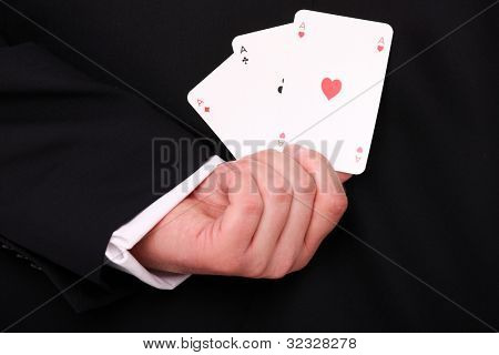 A picture of a young businessman hand holding three aces behind the back