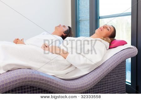 Wellness - a man and a young woman relaxing after sauna, they enjoy the silence