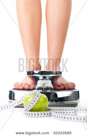 Diet and weight, young woman standing on a scale, only feet to be seen, a apple and a measuring tape