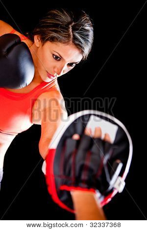 Atheltic woman working out boxing - isolated over a black background
