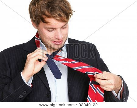 Necktie - man can not tie his tie. Young professional business man trying tying his tie getting ready isolated on white background. Funny young caucasian business man model.
