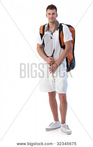 Handsome male tennis player going for training, holding tennis racket, smiling.