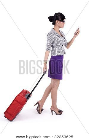 Businesswoman with suitcase and mobile phone