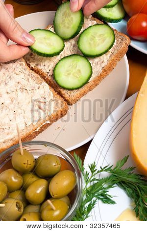 Putting Slices Of Cucumber On Tuna Sandwich