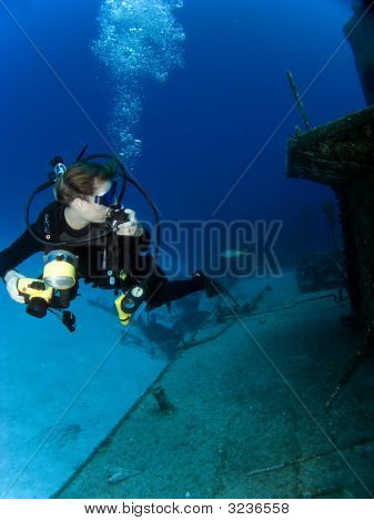 Underwater Photographer Looking At A Sunken Ship