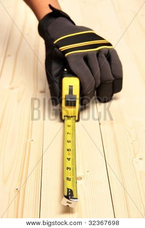 Human Hand Taking Measurement On A Block Of Wood