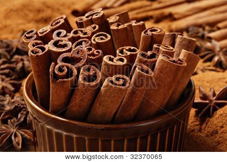 Cinnamon sticks in brown ceramic ramekin with ground cinnamon and star anise in background.  Macro with shallow dof.