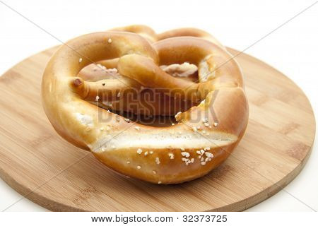 Lye pretzel with salt and wooden plate