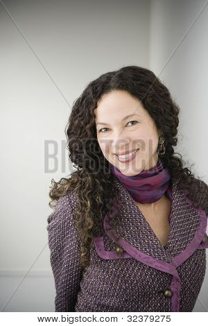 Woman smiling with arms behind back