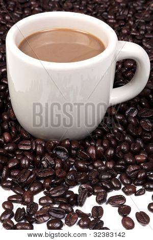Photo of a ceramic mug full of hot coffee surrounded by a mixture of arabica and robusta coffee beans.