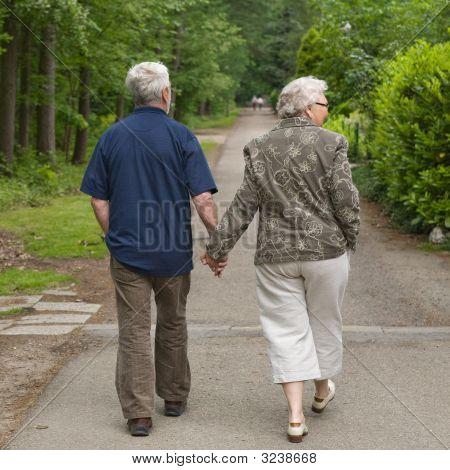 Elderly Couple Walking Hand In Hand