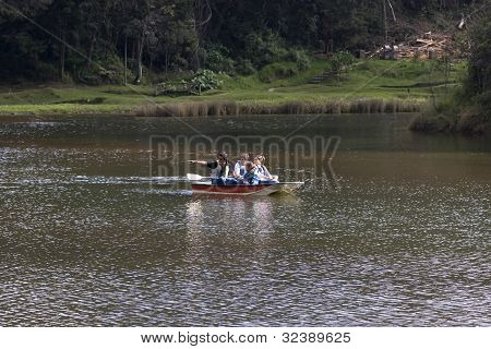 Happy Family Canoeing On Lake