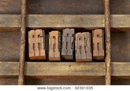ligature - vintage wooden letterpress printing blocks in an old grunge typesetter drawer