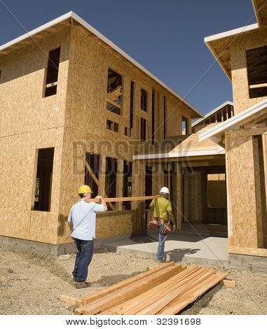 Two construction workers carrying lumber into unfinished building