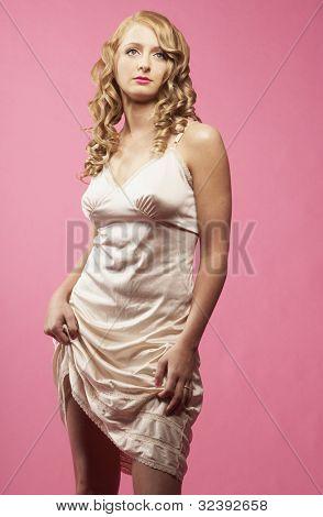 Studio shot of woman pulling up hem of nightgown