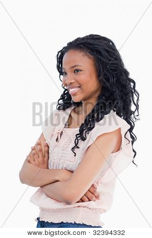 A young smiling woman has her arms folded and is looking away from the camera