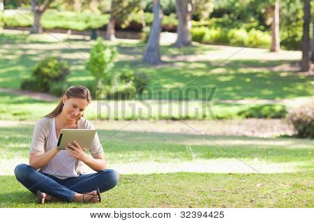 Young woman in the park with a tablet computer