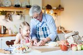Grandmother Is Teaching Kid To Cook Pastries And Bread In Cozy Kitchen At Home. Senior Woman And Lit poster