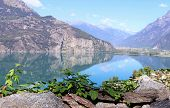 Panoramic View Of A Beautiful And Tranquil Mountain Lake, Green Plant In The Foreground, Nature Back poster