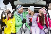stock photo of ski boots  - Teenage Family Sitting In Boot Of Car With Skis - JPG
