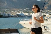 Smiling Mature Woman Running Jogging At Seaside Promenade, Background Sea City, Middle-aged Lifestyl poster