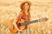 Happy hippie girl stands in a wheat field with her guitar. Spirit of freedom and independence.  poster