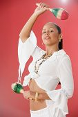 stock photo of maracas  - Studio shot of a female Dominican teenager with maracas - JPG