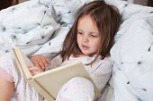 Cute Girl Reading Her Favorite Fairy Tale, Child Sitting In Bed With Book, Kid Preparing To Go To Be poster
