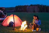 stock photo of tramp  - Tent camping car couple romantic sitting by bonfire night countryside - JPG